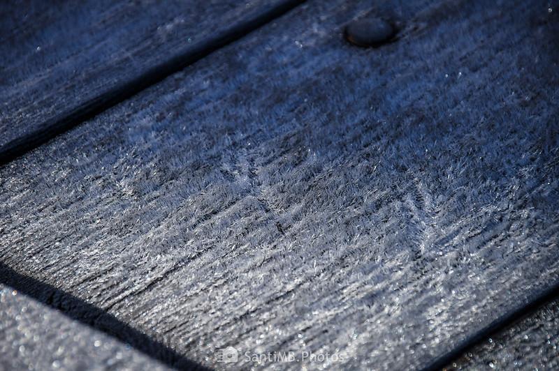 Huellas de pájaro sobre hielo en una mesa de madera