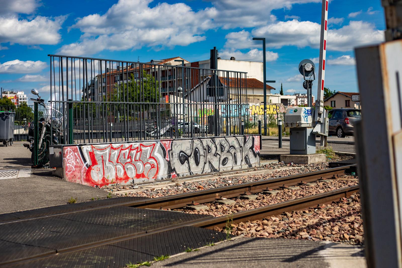 Photographie de graffitis sur un muret de la voie ferrée