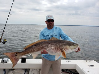 Photo of Man holding a large red drum